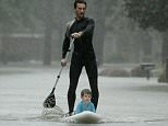 Alexandre Jourde was pictured paddle boarding four-year-old Ethan Colman to safety in a flooded neighborhood in Houston on Monday