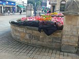 A man lying on a low wall in Lincoln after taking what is believed to be zombie drug Spice