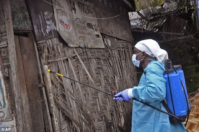 A Liberian health worker spraying disinfectant outside a house before entering and removing the body of a man believed to have died from the Ebola virus in Monrovia. Latest figures show 1,552 deaths from the 3,069 cases reported so far