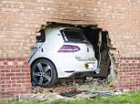 Four people have been injured after a car smashed straight through the wall of a house and set on fire