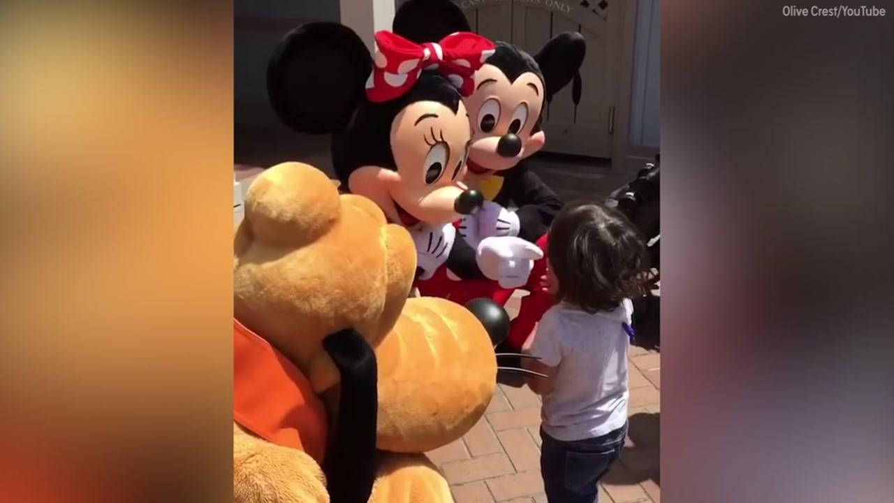 Image of boy hugging mickey, minnie and pluto
