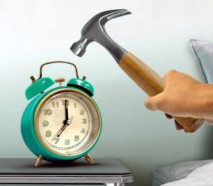 hand hitting alarm clock with hammer; Shutterstock ID 486440014