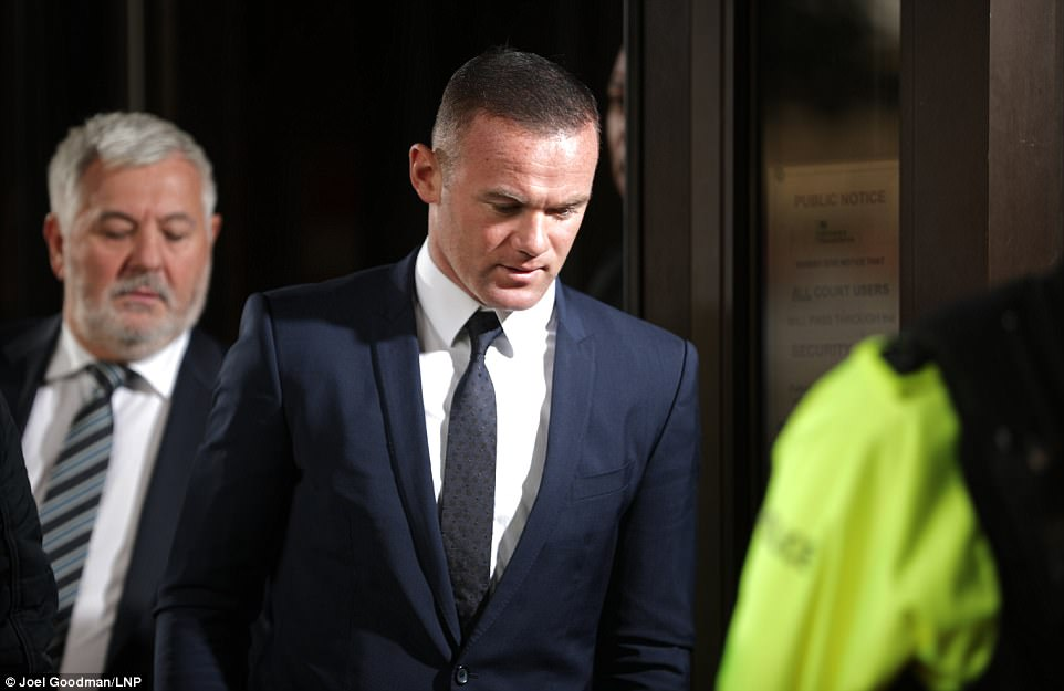 Rooney bows his head as he departs Stockport Magistrates' Court with agent Paul Stretford (pictured left) after pleading guilty to a drink drive charge