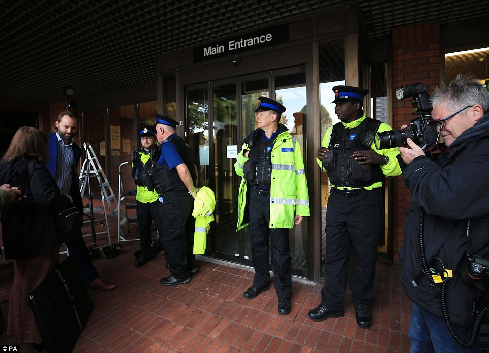 Police wait outside Stockport Magistrates' Court this morning ahead of Rooney's hearing