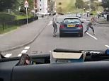 The footage shows the woman, whose name isn't known, repeatedly striking the blue Rover with her handbag as the driver looks on at her