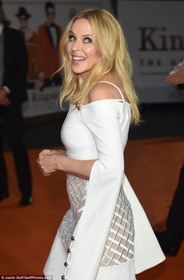 Youthful:The pop queen, 49, looked sensational in an ivory cold-shoulder dress, which featured a daring nude coloured panel, covered with silk patterns, which gave the illusion that the star was flashing her midriff and the top of her toned legs