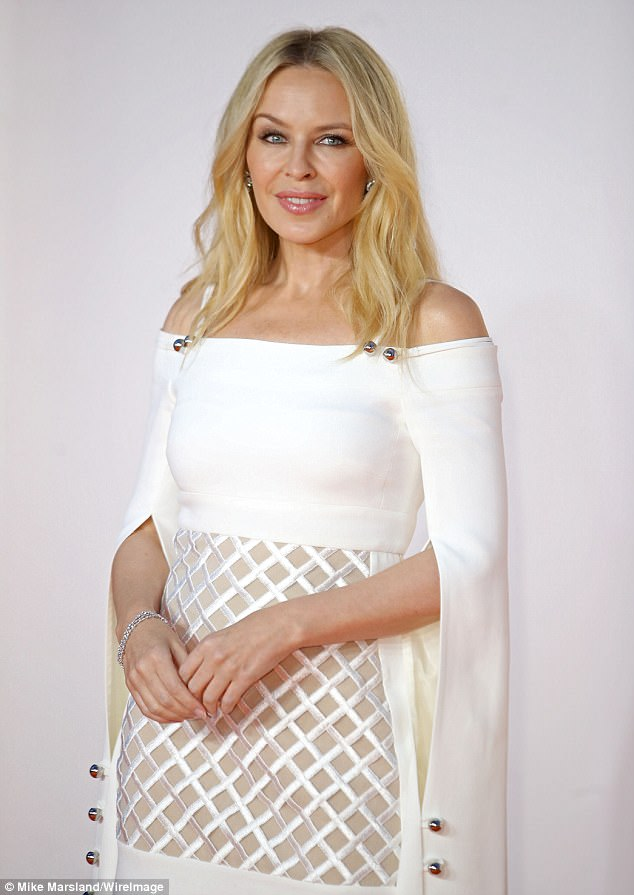 Fit for a pop queen: Kylie looked dazzling in her ivory gown, and accessorised with a crystal bracelet