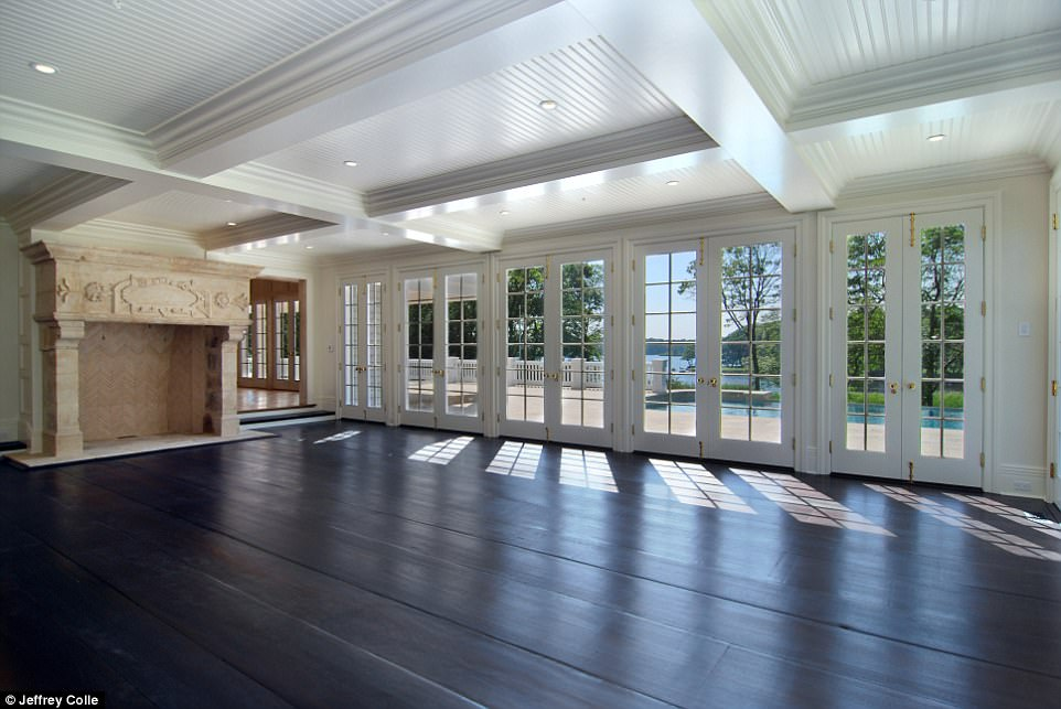 A family room with fireplace overlooks the pool and pond with more French doors