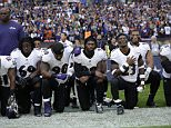 Some members of the Oakland Raiders sit on the bench during the national anthem on Sunday night .The whole team and the coaches were in solidarity, either sitting or linking arms during the singing