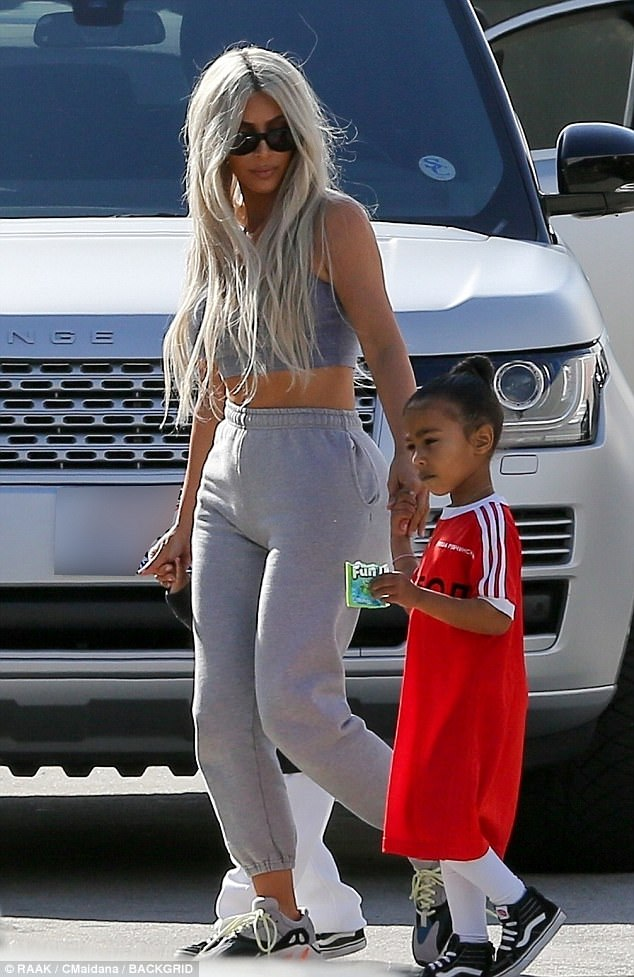 Mommy's girl: North was enjoying a snack while heading with mom Kim and son Saint