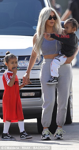 Doting mom: Kim flaunted her flat midsection and her ample cleavage in a simple top in a dark gray tone