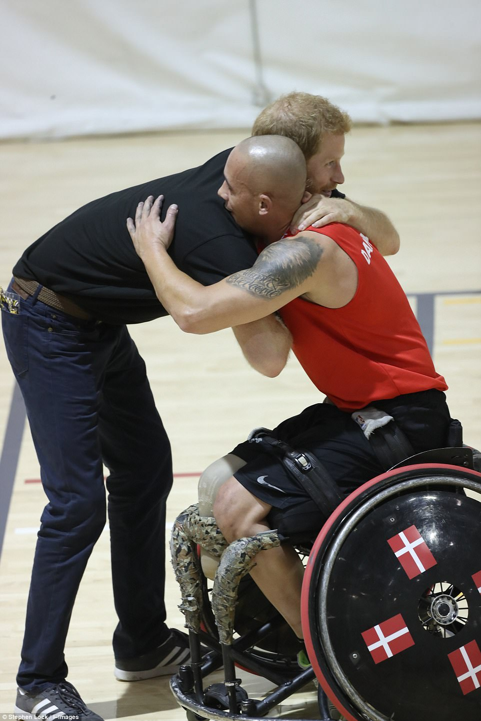Harry the hugger: The prince is counting down to the opening of the Invictus Games - and went to a training session where he hugged one of the wheelchair athletes taking part