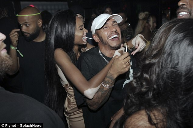 Cosy: Her striking good looks have even caught the eye of Formula One hunk Lewis Hamilton and the pair have frequently been spotted partying together