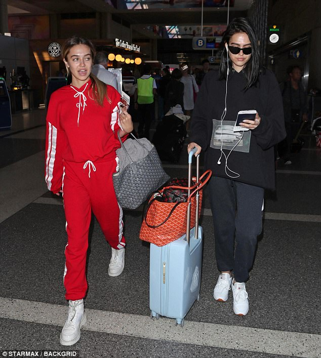 Travelling light:Delilah opted for red sweat pants, a matching sweatshirt, sunglasses, and had her belongings packed into a tote bag