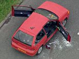 An aerial photograph shows the car with bullet holes in the bodywork and shattered glass lying on the tarmac. A handgun can be seen lying on the roof of the vehicle