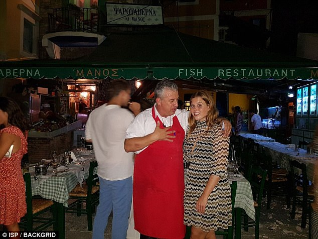 The princess posed for photos with the waiter outside the Greek restaurant on the island