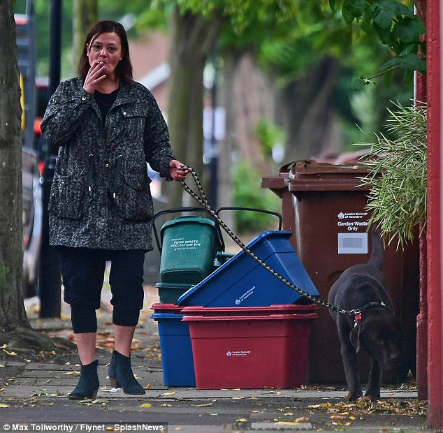 Having a break: Lisa Armstrong defiantly stepped out on Wednesday to grab fresh air with their dog Hurley while casually enjoying a cigarette in London
