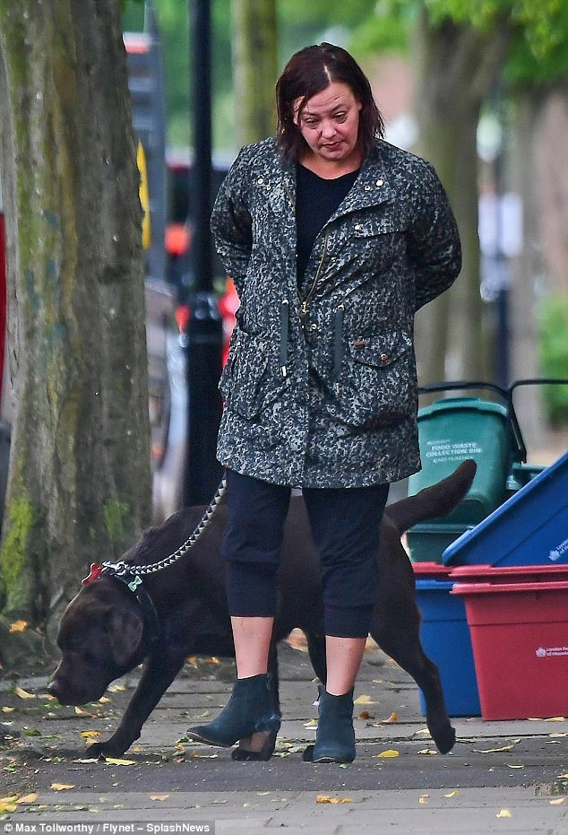Stepping out: Wrapping up for the cooler temperatures, she donned a printed raincoat which highlighted her cropped black leggings alongside her chocolate-coloured labrador