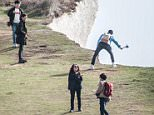 Hyewon Kim had asked a stranger to take her picture but lost her footing as she landed and toppled over the Seven Sisters cliffs (pictured, sightseers pose by the cliffs today)