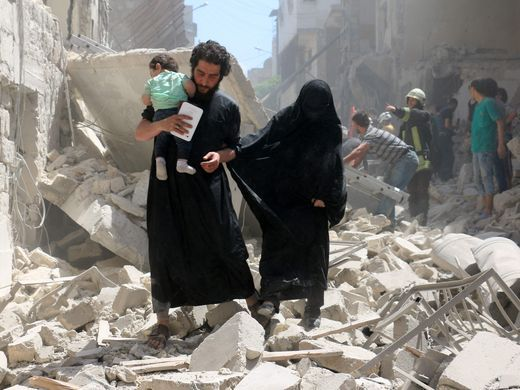 A family walks amid the rubble of destroyed buildings