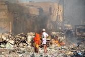 A man and woman look at the damages on the site of the explosion of a truck bomb in the centre of Mogadishu, on October 14, 2017 (Mohamed Abdiwahab/AFP)