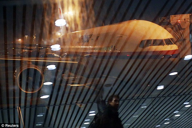 How MH370 would have looked: Flight MH318 to Beijing sits on the tarmac as passengers are reflected on the glass at the boarding gate at Kuala Lumpur International Airport in the early hours of Monday