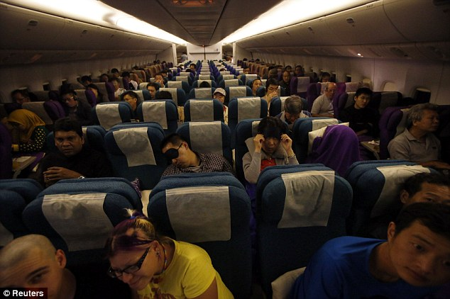 Tracing the journey: Passengers in their seats onboard Malaysia Airlines Boeing 777-200ER flight MH318 as it cruises towards Beijing at approximately 1.30am on Monday. MH318 replaces the flight number of the missing airplane, MH370, as a mark of respect to the passengers and crew
