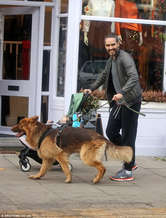 Loving life:With one hand on the buggy and one holding onto his pet dog, Bear, the 42-year-old comedian seemed in high spirits