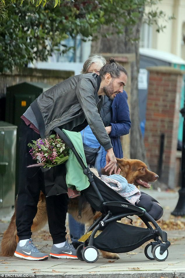 Adorable: Russell cooed over his little one as he tickled her tummy in the pram
