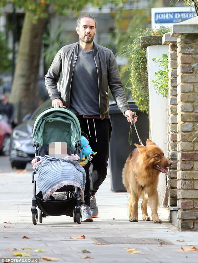 Chirpy: Russell Brand looked in good spirits as he headed for a stroll with his 11-month-old daughter Mabel in London on Tuesday