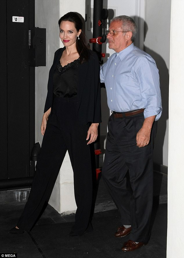 Stunning: Angelina rocked all-black including a silky top featuring a lacy neckline, trousers, heels and blazer as the older mystery man walked with his arm around her