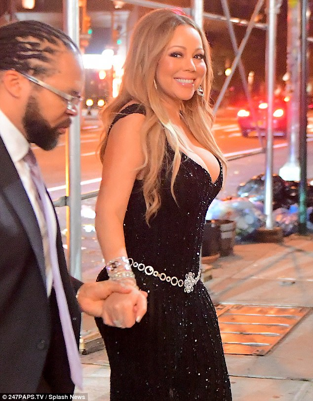 Glamour; Mariah cracked a beaming smile as she held onto the hand of her bodyguard