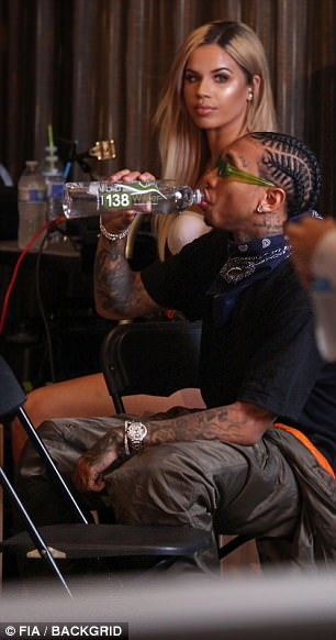 Taking a break: Earlier in the day, the rap artist was pictured sipping on the flavored water in between scenes alongside a blonde beauty