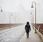 Carol Minger walks on the Stone Arch Bridge as it snows in Minneapolis, Friday, Oct. 27, 2017. The snowfall was the first of the season. (Renee Jones Schneider/Star Tribune via AP)
