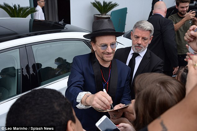 Chance of a lifetime: Everyone wanted to meet U2 frontman Bono as he signed autographs before heading to the ceremony