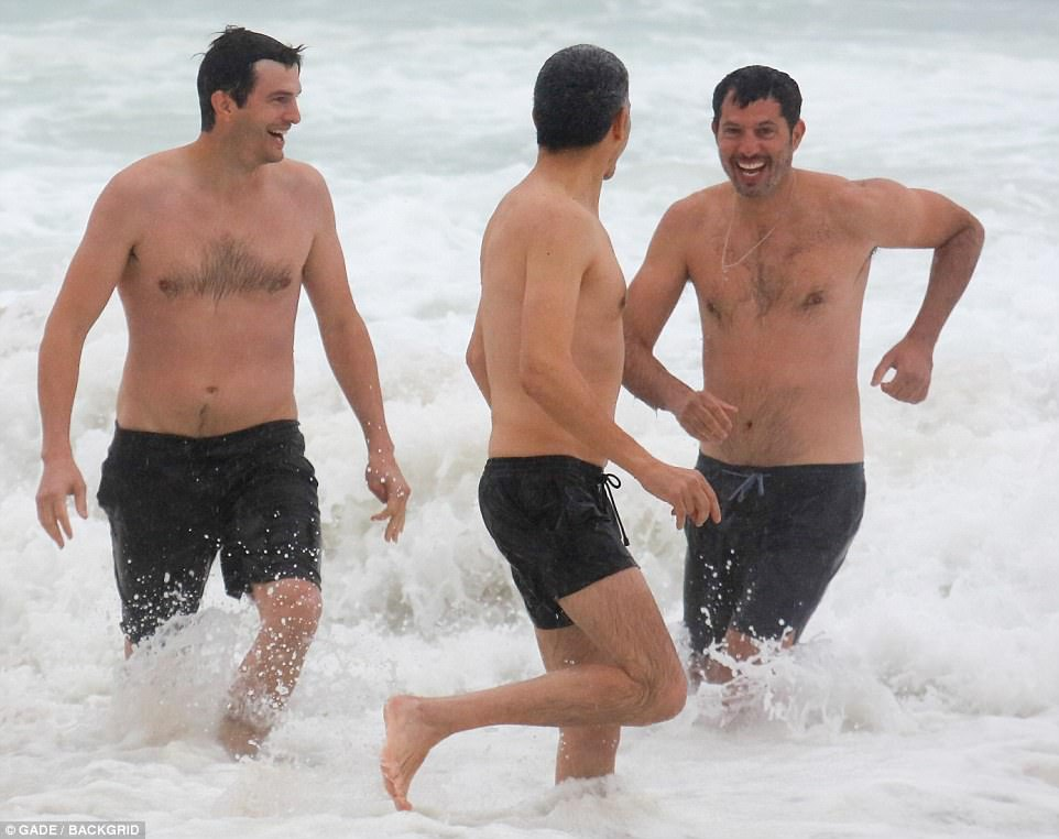 Wave runners: Ashton and a pal (center) chased Madonna's manager and film producer Guy Oseary (right) through the waves ahead of his wedding vow renewal to model wife Michelle