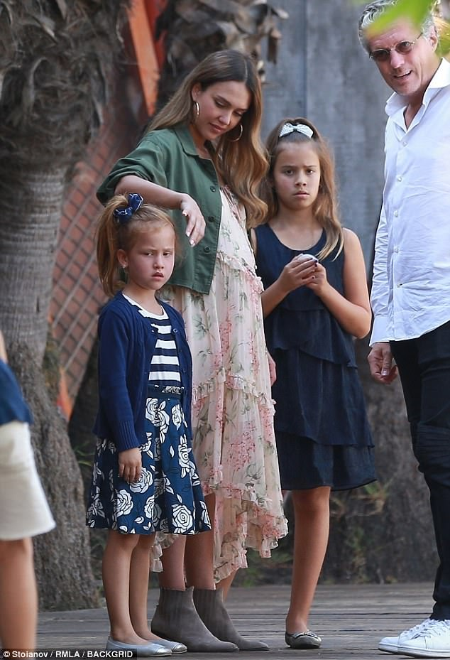 Her daughters were coordinated in navy ensembles, with Honor wearing a sleeveless tiered dress and Haven styled in a striped and floral number