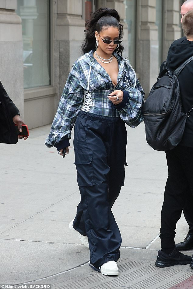 Dropping jaws: Rihanna put her edgy fashion sense - and cleavage - on full display as she stepped out in New York City on Friday, in a funky plunging outfit that showcased her assets