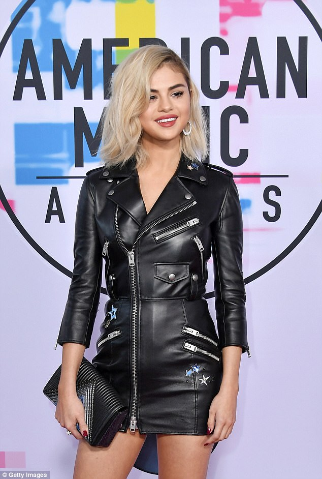 Big reveal: Selena, who unveiled her lighter locks at the Sunday awards show, flaunted her legs in an edgy black and silver leather dress