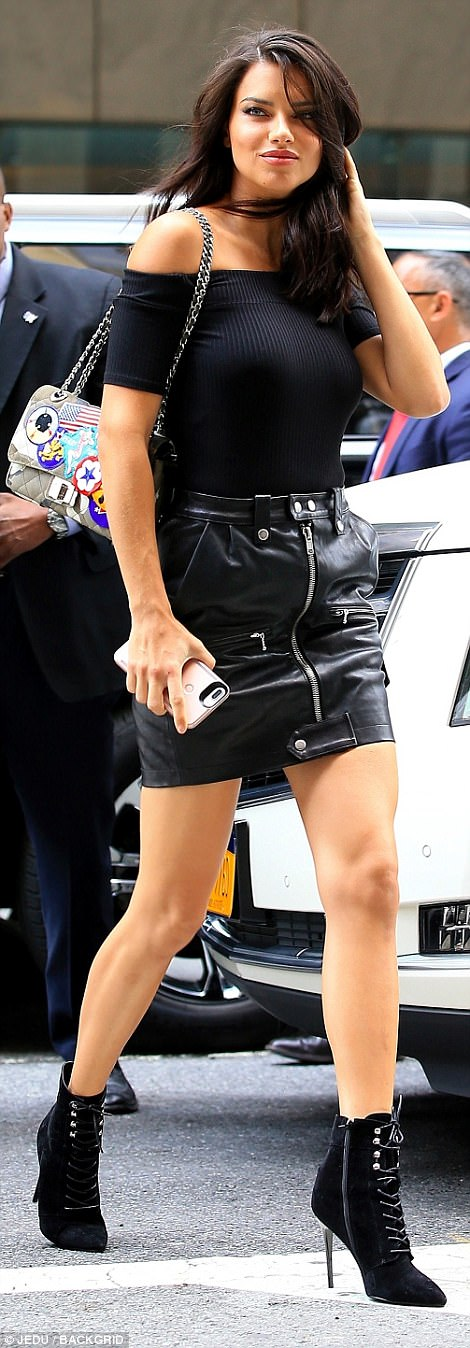 Beauty: The 36-year-old cut an edgy figure as she teamed together a form-fitting ribbed bandeau top that she tucked into a grunge leather mini-skirt that boasted zip detailing across the front