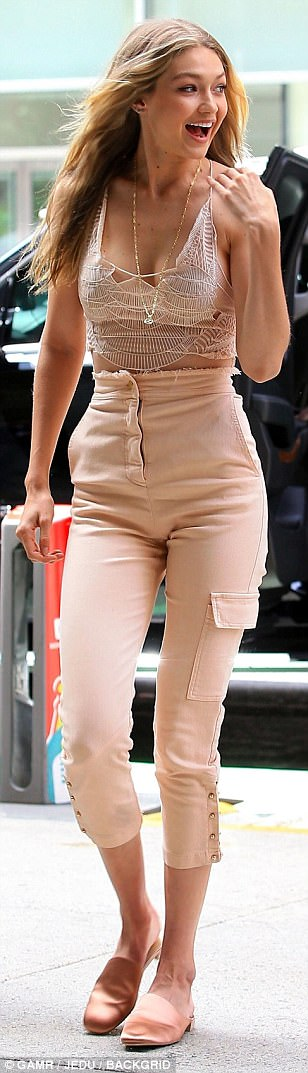 Hamming it up: The model, who is dating former One Direction star, Zayn Malik flashed a smile as she playfully flicked her hair while strutting her way into the important meeting ahead of November's showcase