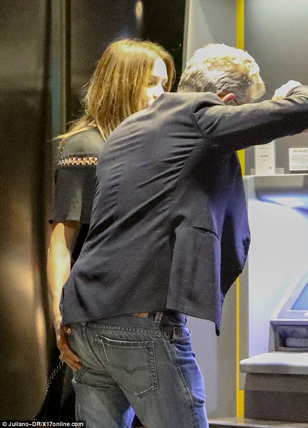 Quite the handful:As he leaned in toward the ATM machine, she placed her hand on firmly on his derriere with the pair putting on a very affectionate display