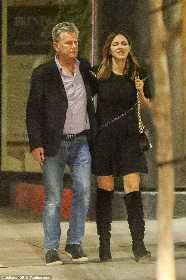 Good times:Katharine cut a stylish figure in thigh-high boots with a matching black dress, adding a chain link purse
