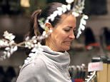 Kirsty Gallacher grimaces as she looks through charity shop clothes during community service