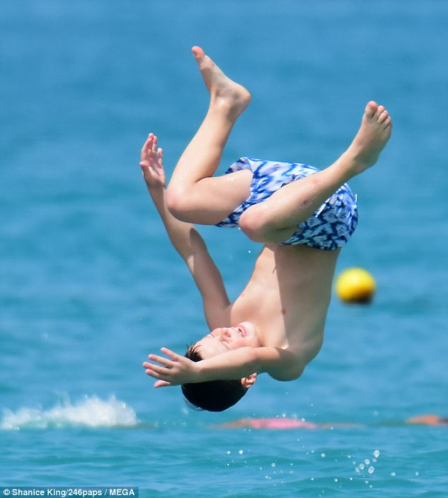 Loving life: Their eldest son Kai, seven, couldn't resist showing off his impressive acrobatic skills as he did a somersault into the glistening blue waters of Barbados on Tuesday