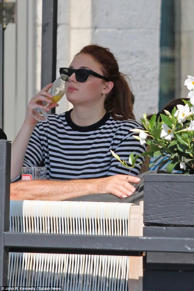 Relaxed: The British beauty cut a relaxed figure as she dined outdoors with her family, wearing a monochrome Breton top while she sipped on her beverage