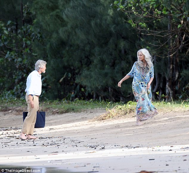 Beachwear: Meanwhile, the grizzled and bearded Michael wore a powder blue shirt with its sleeves folded up, tucking the top into khaki trousers
