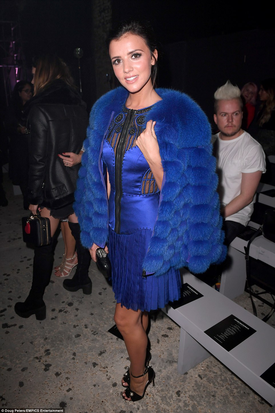 Finishing touches: Lucy oozed confidence as she posed at the bash, with a chic fluffy coat to match her dress layered on top later on
