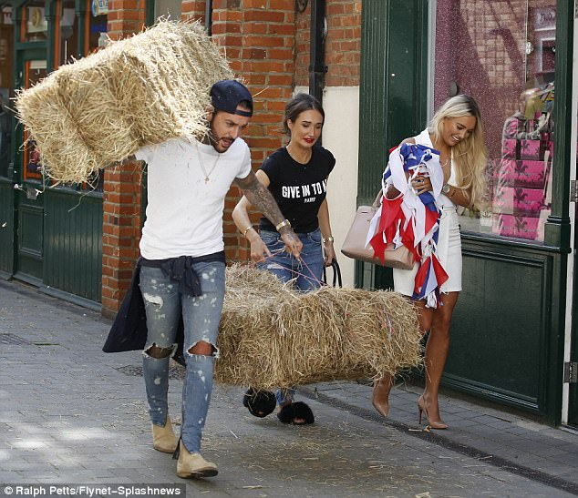 Heavy work: She appeared to struggle as she joined her beau in carrying the hay, while Amber cheekily chose to carry the American-themed bunting instead