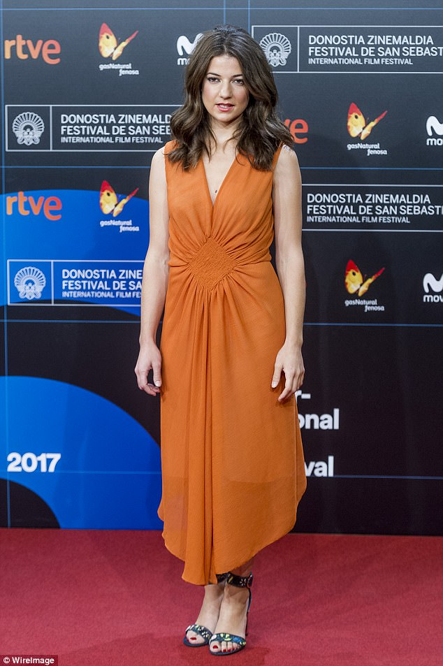 Bold in brights: Esther Garrel looked chic in a vivid orange dress and floral strappy heels